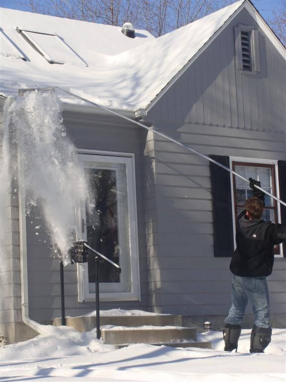 raking snow off a home's roof with a roof rake