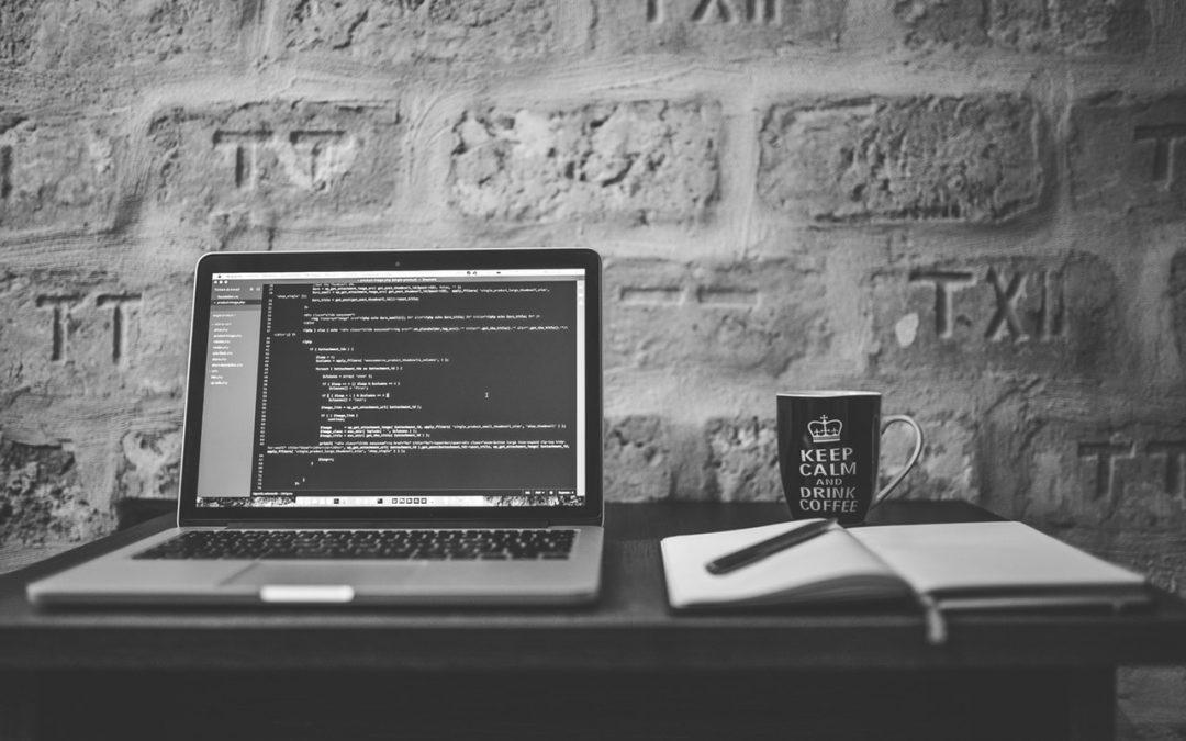 laptop, notebook, and keep calm mug on desk